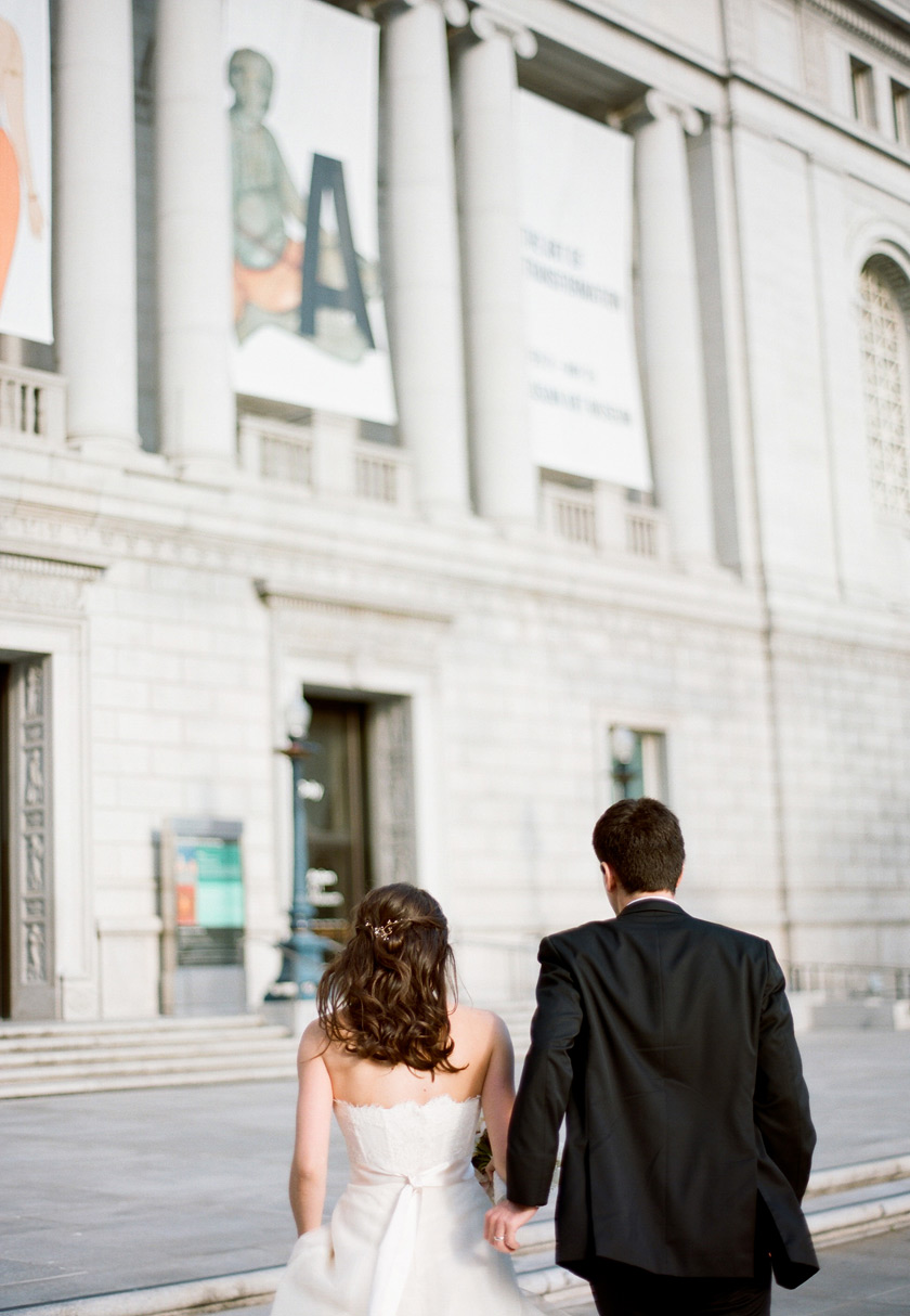 A married couple walk to their wedding reception at the asian art museum in san francisco